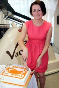 Właścicielka Studio Figura, szczęśliwa kroi tort z okazji urodzin swojego biznesu
