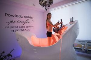 dziewczyna ćwiczy na infra shaper swan, urządzenie działa wielofunkcyjnie dzięki temu, że generuje promieniowanie podczerwone oraz światło kolagenowe. Dodatkowo eliptyk skrętny pozwala na ćwiczenia wszystkich partii ciała