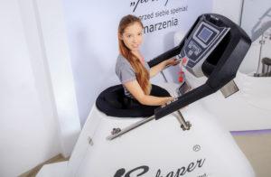 Kobieta ćwicząca na Vacu Shaper bieżnia generująca próżnię podciśnienia przez co organizm dużo lepiej spala tłuszcz i modeluje sylwetkę