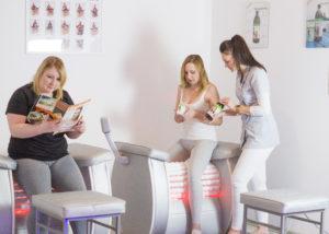 Kobiety ćwiczące na roll shaper, czytające magazyn studio figura oglądające set oczyszczający